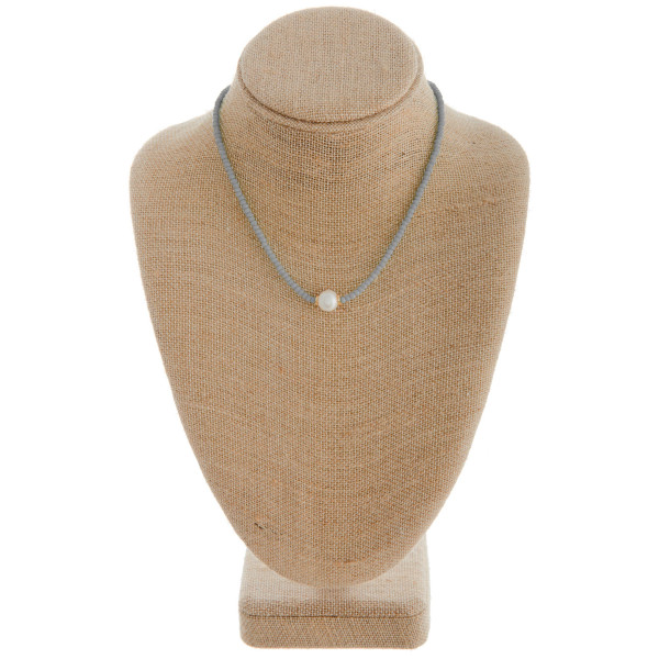 "Short grey beaded necklace featuring a pearl accent. Measures approximately 16"" in length."