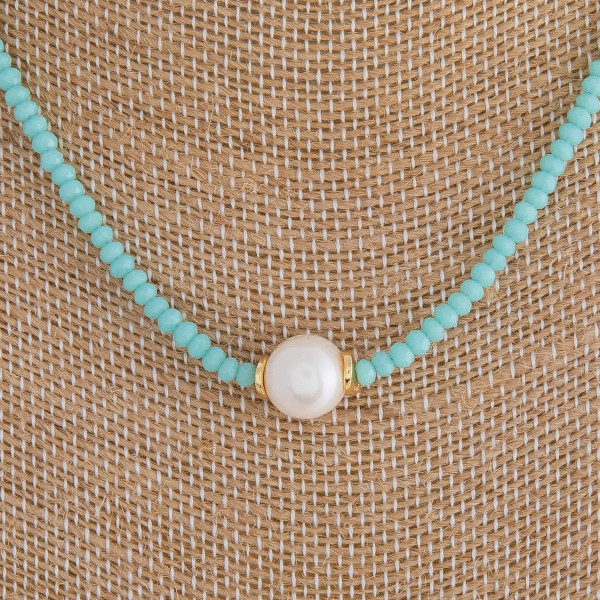 "Short blue beaded necklace featuring a pearl accent. Measures approximately 16"" in length."