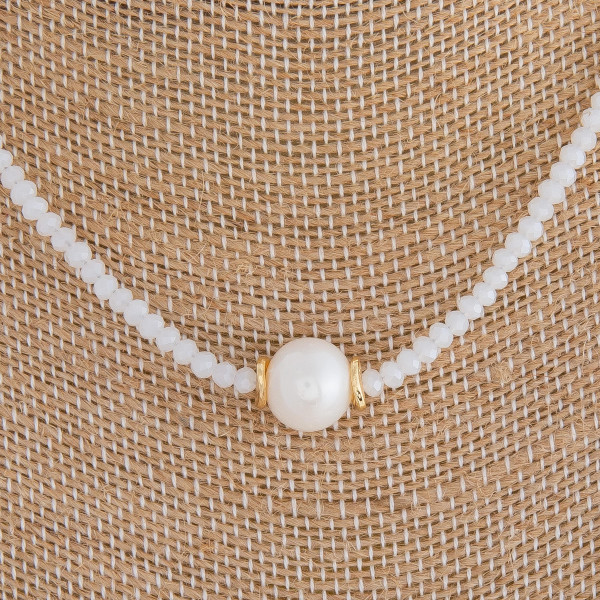 "Short white beaded necklace featuring a pearl accent. Measures approximately 16"" in length."