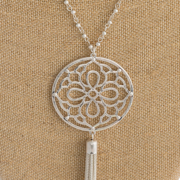 """Long metal necklace featuring a circular pendant with filigree inspired details and a tassel accent. Pendant approximately 5"""". Approximately 42"""" in length overall."""