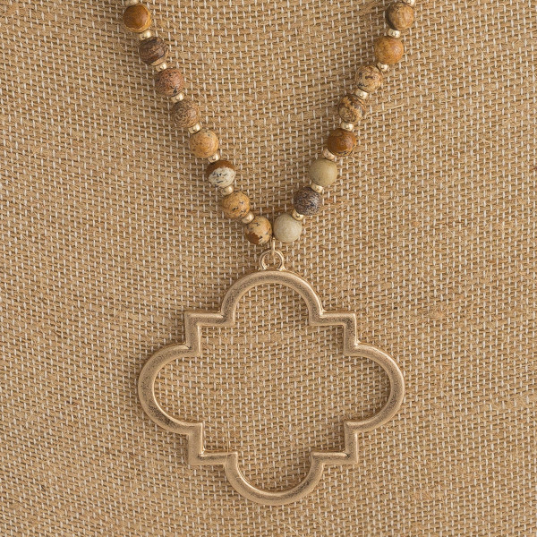 "Long necklace featuring a lotus clover inspired metal pendant with natural stone beaded accents. Pendant approximately 2.5"" in diameter. Approximately 36"" in length overall."