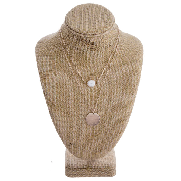 "Two layered metal necklace featuring a circular pendant and pearl accent. Shortest layer approximately 14"". Approximately 18"" in length overall."