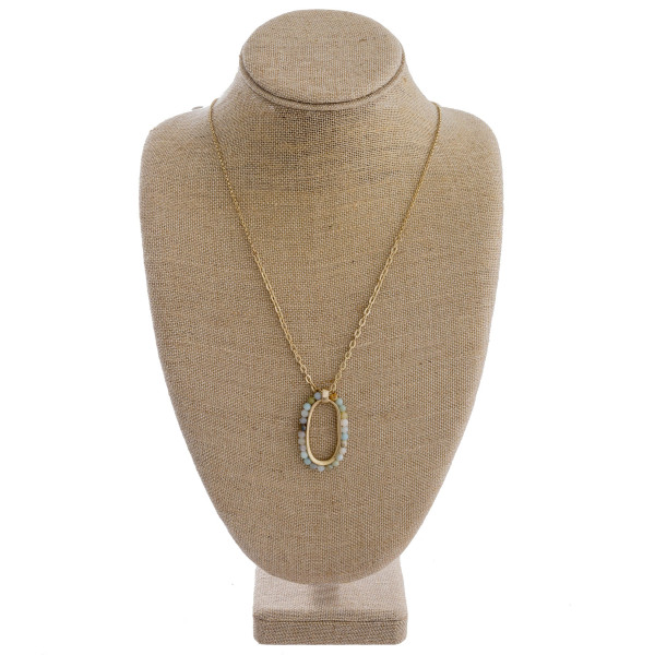 "Long gold necklace featuring an oblong pendant with beaded accents. Pendant approximately 2"". Approximately 34"" in length overall."