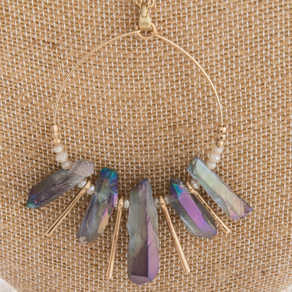 """Long gold metal necklace featuring a circular pendant with grey natural stones, metal tassels and beaded accents. Pendant approximately 3"""" in length. Approximately 38"""" in length."""