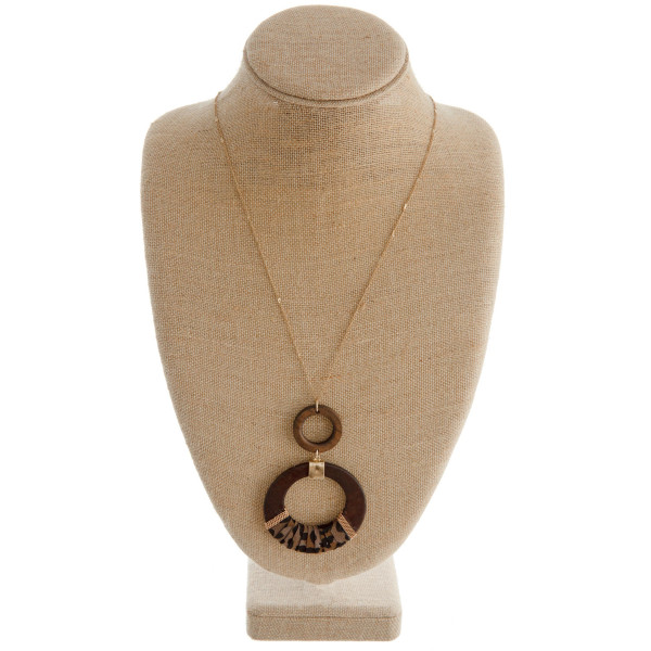 """Long gold chain necklace featuring a circular pendant with faux leather animal print accents. Pendant approximately 4"""". Approximately 42"""" in length."""