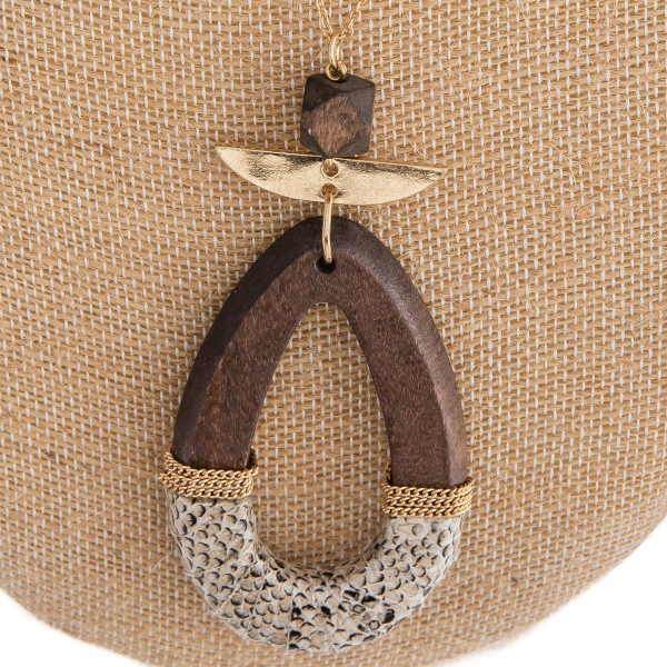 """Long gold chain necklace featuring a wooden teardrop pendant with snakeskin details. Approximately 36"""" in  length. Pendant is approximately 3"""" in length and 1.5"""" in diameter."""