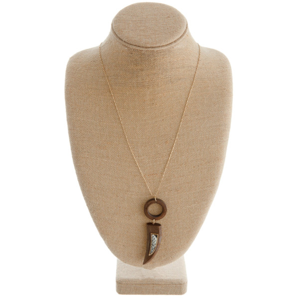 """Long gold chain necklace featuring a horn / tusk pendant with faux leather animal print accents. Pendant approximately 4"""". Approximately 42"""" in length."""