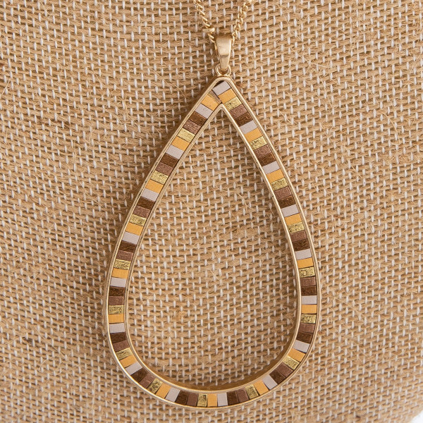 """Gold metal necklace featuring a teardrop pendant with resin detail. Pendant approximately 3"""". Approximately 38"""" in length."""