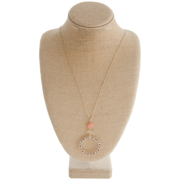 """Gold metal necklace featuring a circular pendant with resin detail and a natural stone accent. Pendant approximately 3"""". Approximately 38"""" in length."""