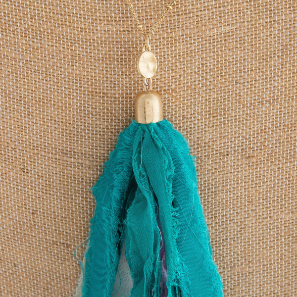 "Long gold chain necklace featuring a green fabric tassel. Approximately 36"" in length. Tassel is approximately 6"" in length."