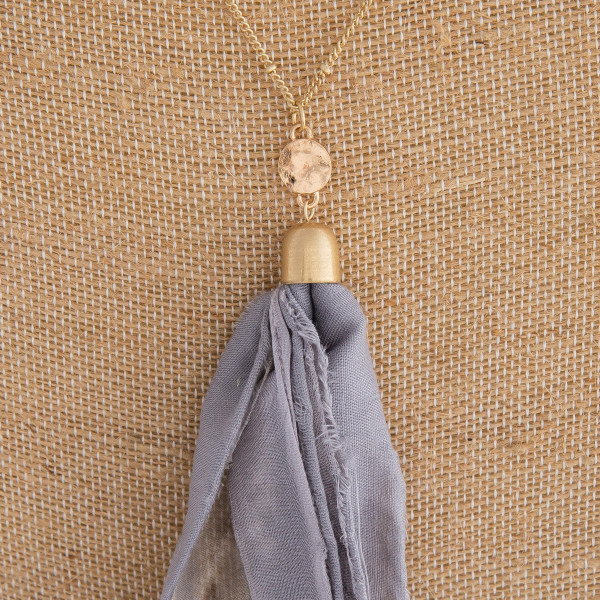 "Long gold chain necklace featuring a grey fabric tassel. Approximately 36"" in length. Tassel is approximately 6"" in length."