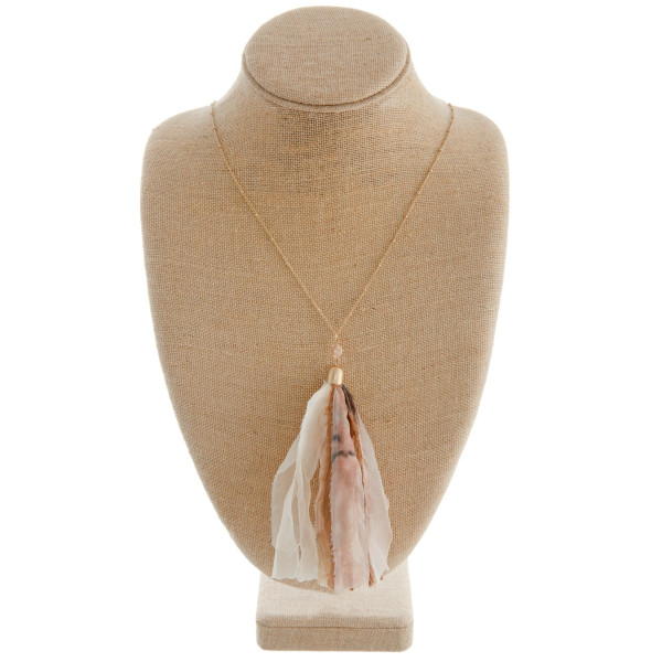 "Long gold chain necklace featuring a natural fabric tassel. Approximately 36"" in length. Tassel is approximately 6"" in length."