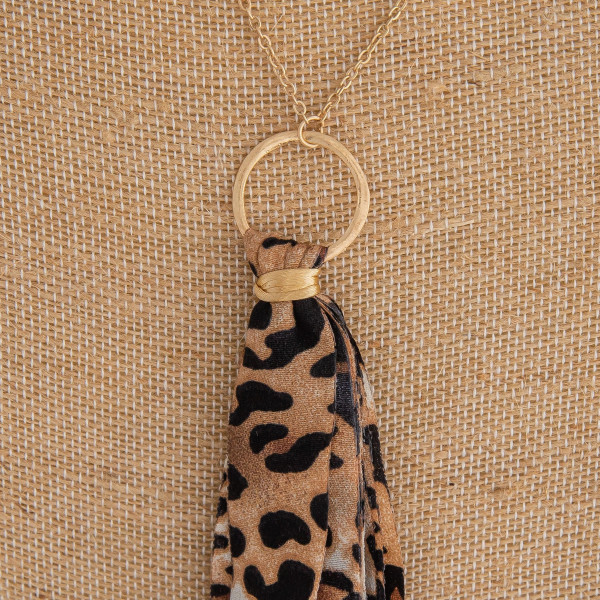 "Long gold chain necklace featuring a fabric cheetah print tassel. Approximately 36"" in length. Tassel is approximately 6"" in length."