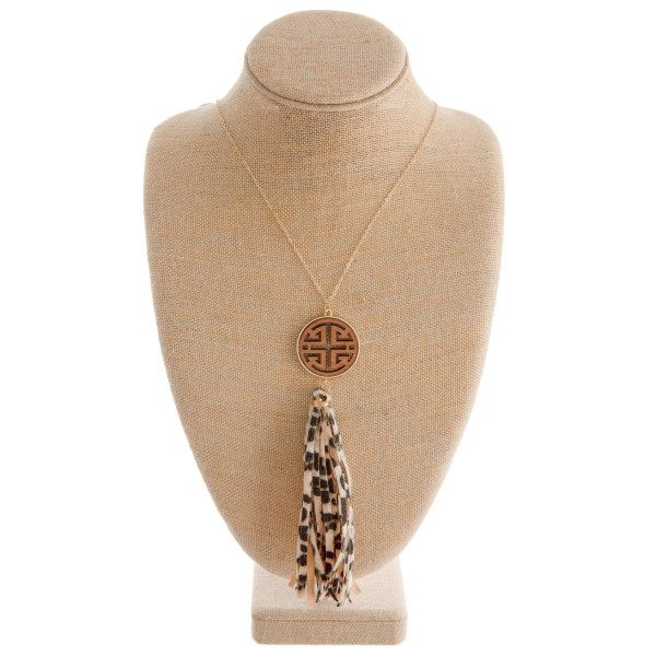 "Long gold chain necklace featuring a circular pendant with wood accents and a fabric cheetah print tassel. Approximately 36"" in length."