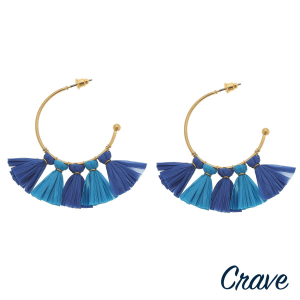 """Gold hoop earrings featuring blue resin tassel accents. Approximately 1.5"""" in diameter."""