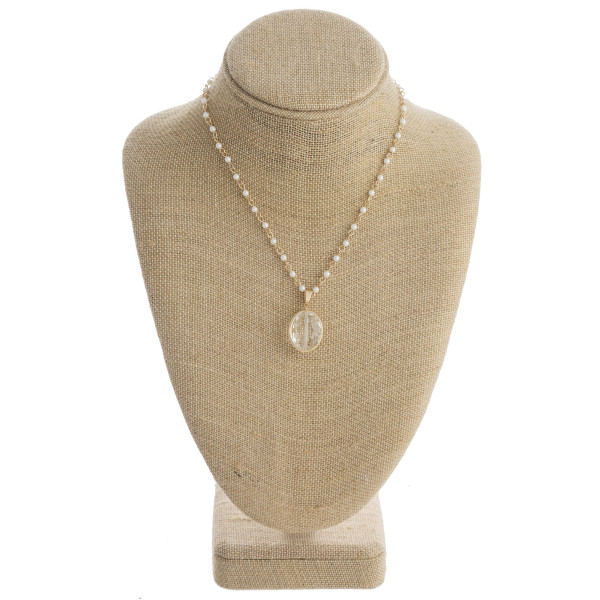 """Gold chain link necklace featuring iridescent beaded details and a clear crystal pendant. Pendant approximately 1"""". Approximately 16"""" in length."""