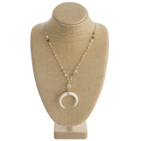 """Long gold chain necklace featuring beaded accents and a large crescent pendant. Approximately 36"""" in length. Crescent pendant is approximately 2"""" in diameter."""