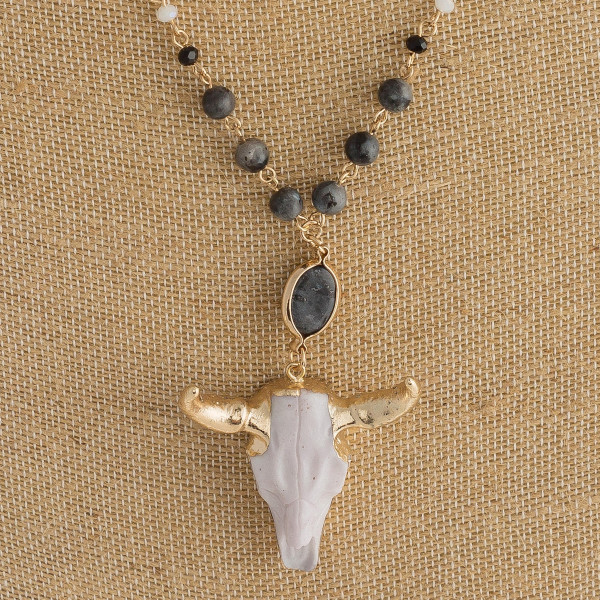 "Long gold chain necklace featuring bead accents and a cow skull pendant. Approximately 35"" in length. Pendant is approximately 2"" in length."