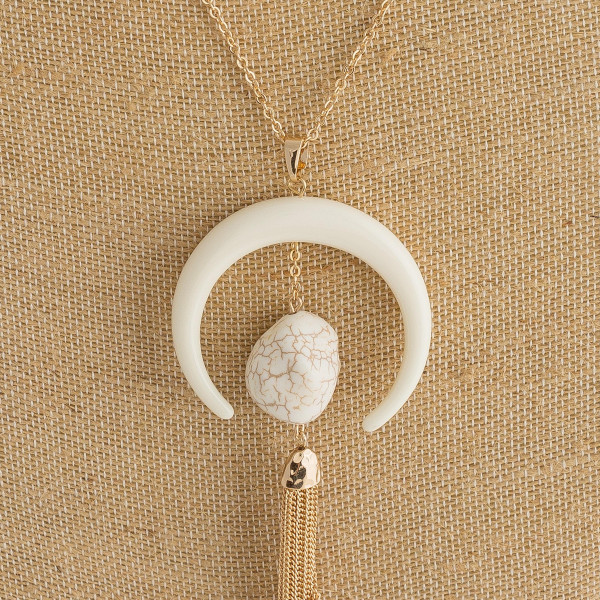 "Long cable chain necklace featuring a large crescent pendant, a natural stone accent, and a gold chain tassel. Crescent pendant is 2"" in diameter. Approximately 36"" in length overall."