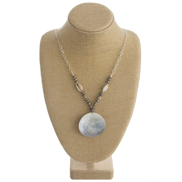 """Long silver chain necklace featuring bead and puka shell accents, and a black mother of pearl inspired disc. Approximately 36"""" in length."""
