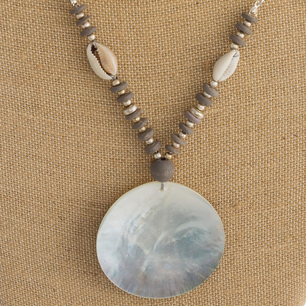 "Long silver chain necklace featuring bead and puka shell accents, and a black mother of pearl inspired disc. Approximately 36"" in length."