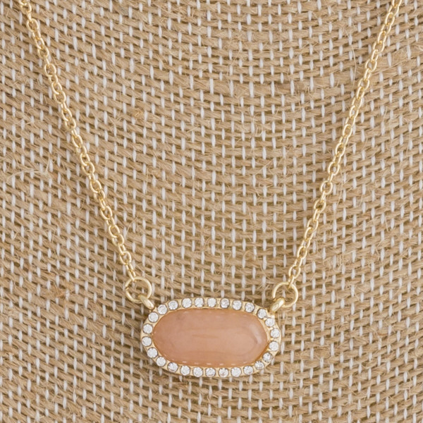"Gold metal necklace featuring a orange natural stone horizontal pendant with cubic zirconia details. Pendant approximately .5"". Approximately 16"" in length overall."