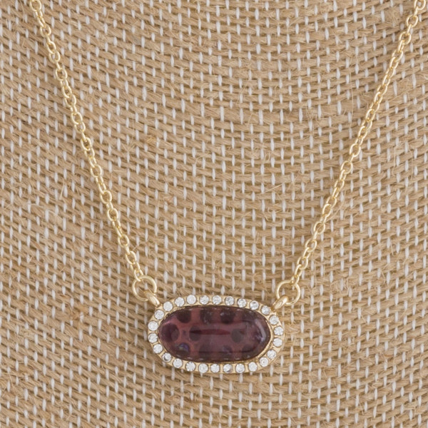 "Gold metal necklace featuring a purple natural stone horizontal pendant with cubic zirconia details. Pendant approximately .5"". Approximately 16"" in length overall."