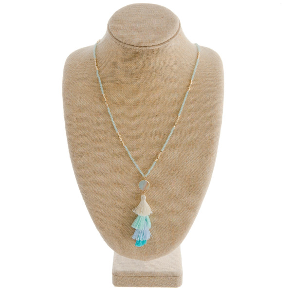 "Long gold chain necklace with gold and glass bead details featuring an amazonite stone and a fanned tassel. Measures approximately 36"" in length."