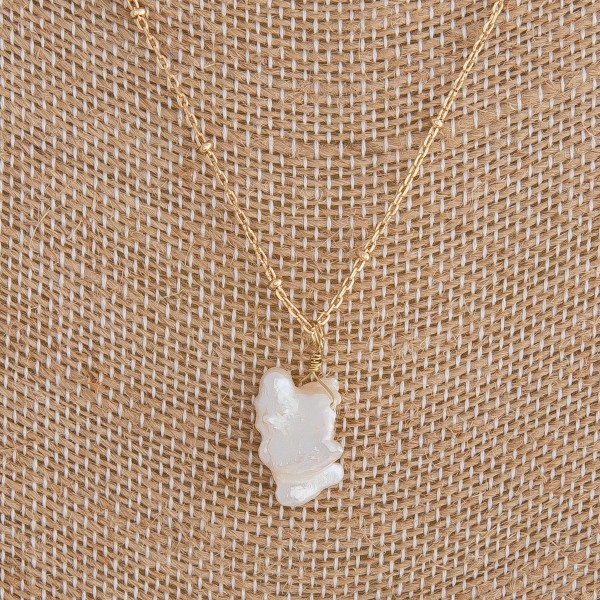 """Gold necklace featuring a baroque pearl accent. Measures approximately 18"""" in length."""