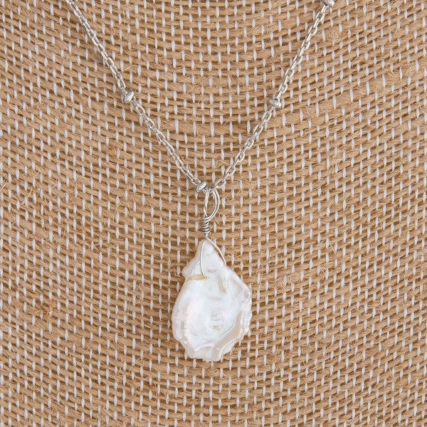 """Silver necklace featuring a baroque pearl accent. Measures approximately 18"""" in length."""