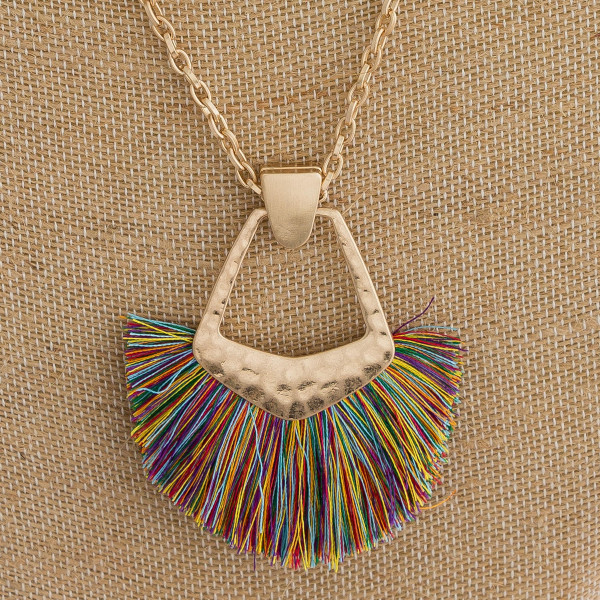 "Long cable chain necklace featuring a metal pendant with tassel details. Pendant approximately 3"". Approximately 34"" in length overall."
