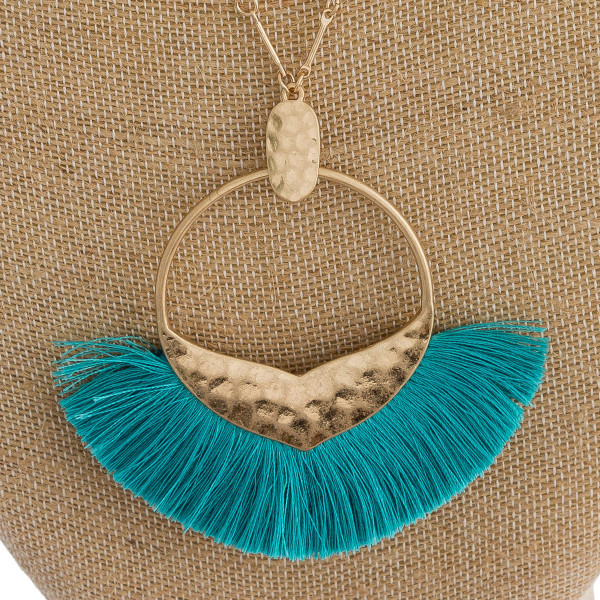 """Long cable chain necklace featuring a circular metal pendant with a mermaid tale detail and tassel accents. Pendant approximately 3.5"""". Approximately 40"""" in length overall."""