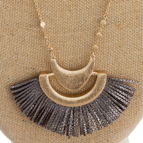 """Long cable chain necklace featuring a faux leather tassel inspired pendant with gold metal accents. Pendant approximately 3"""" x  2.5"""". Approximately 34"""" in length overall."""