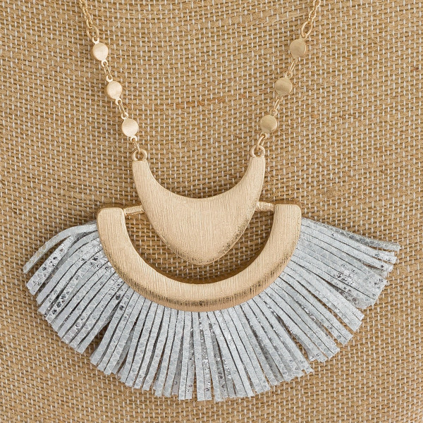"""Long cable chain necklace featuring a faux leather tassel inspired pendant with metallic snakeskin details and gold metal accents. Pendant 3"""" x 2.5"""". Approximately 34"""" in length overall."""