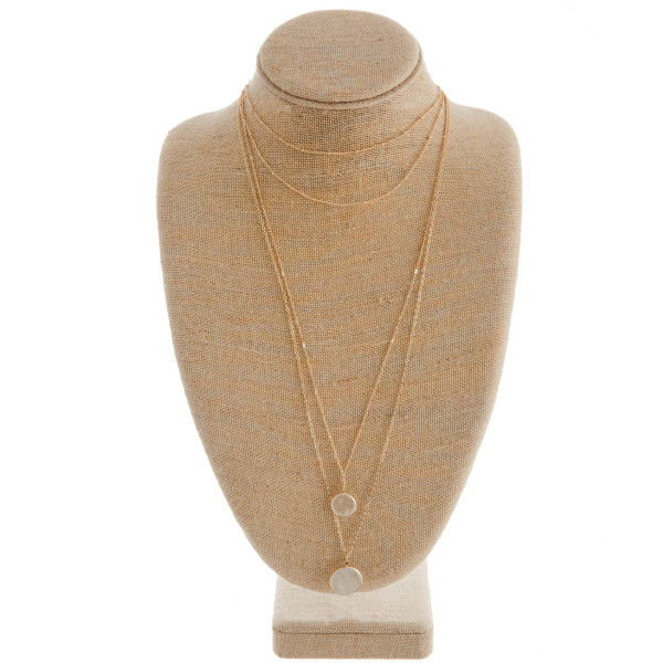 "Gold metal layered necklace featuring a clear quartz inspired stone pendant. Approximately 36"" in length."