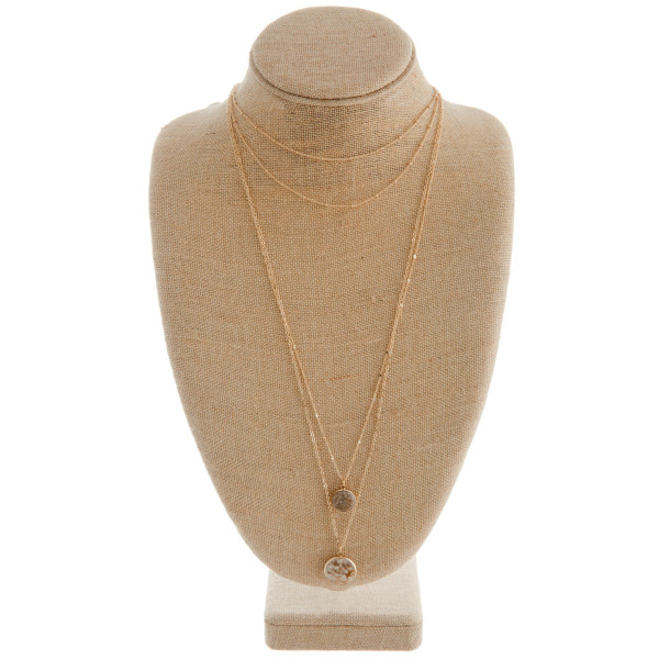 "Gold metal layered necklace featuring a fire quartz inspired stone pendant. Approximately 36"" in length."