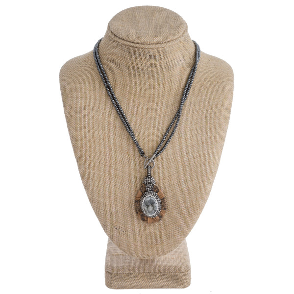 """Two layered beaded necklace featuring a faux leather snakeskin pendant with a druzy natural stone center detail with rhinestone accents and a toggle clasp closure. Pendant approximately 2.5"""". Approximately 20"""" in length overall."""