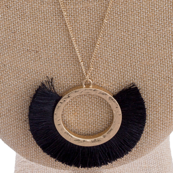 "Long double layered metal necklace featuring a circular pendant with tassel details. Shortest layer approximately 16"" in length. Pendant approximately 2.5"". Approximately 32"" in length."