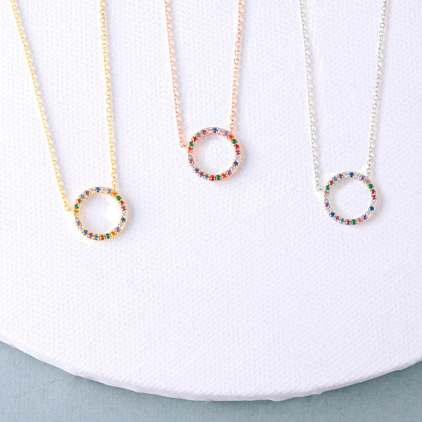 "Dainty cable chain necklace featuring a circular pendant with multicolor cubic zirconia details. Pendant approximately .5"" in diameter. Approximately 18"" in length overall."
