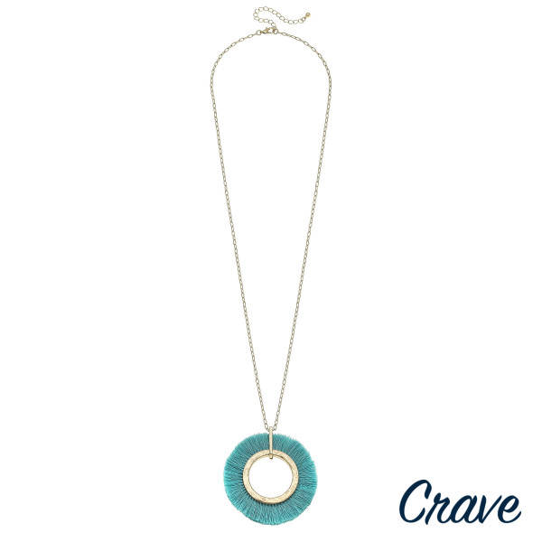 "Long metal necklace featuring a circular pendant with aqua tassel details and gold accents. Pendant approximately 2.5"". Approximately 36"" in length overall."