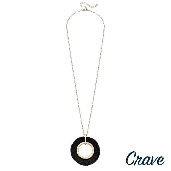 "Long metal necklace featuring a circular pendant with black tassel details and gold accents. Pendant approximately 2.5"". Approximately 36"" in length overall."