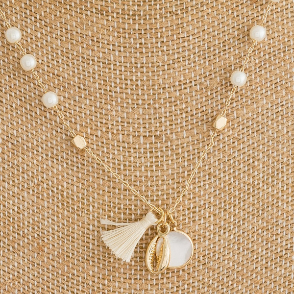 "Dainty metal necklace featuring pearl beaded details with a tassel, pearl, and puka shell accents. Approximately 16"" in length."