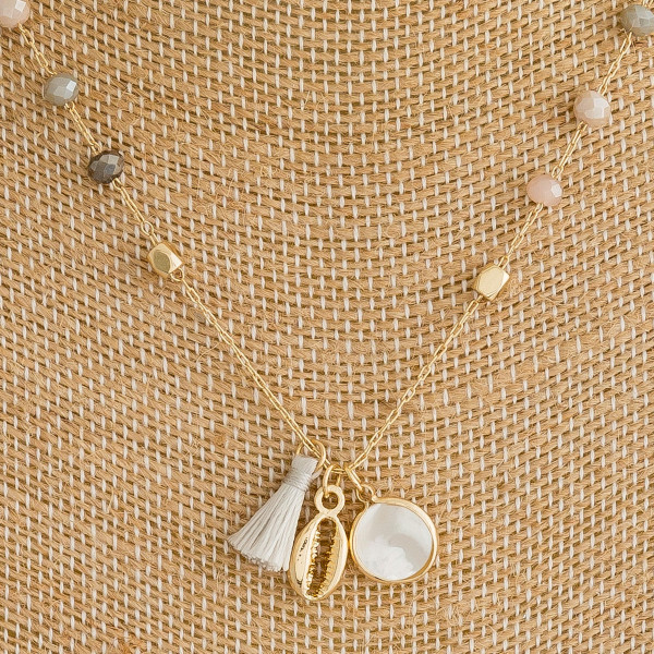 "Dainty metal necklace featuring natural faceted bead details with a tassel, pearl, and puka shell accents. Approximately 16"" in length."