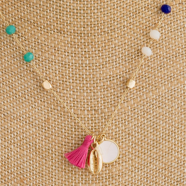 "Dainty metal necklace featuring multicolor faceted bead details with a tassel, pearl, and puka shell accents. Approximately 16"" in length."
