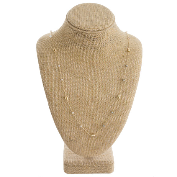 "Long dainty metal necklace featuring puka shell and natural faceted bead details. Approximately 30"" in length."