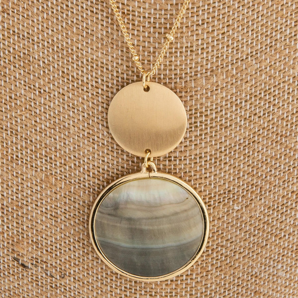"""Long metal necklace featuring a mother of pearl inspired pendant with a gold accent. Pendant approximately 2"""". Approximately 36"""" in length overall."""