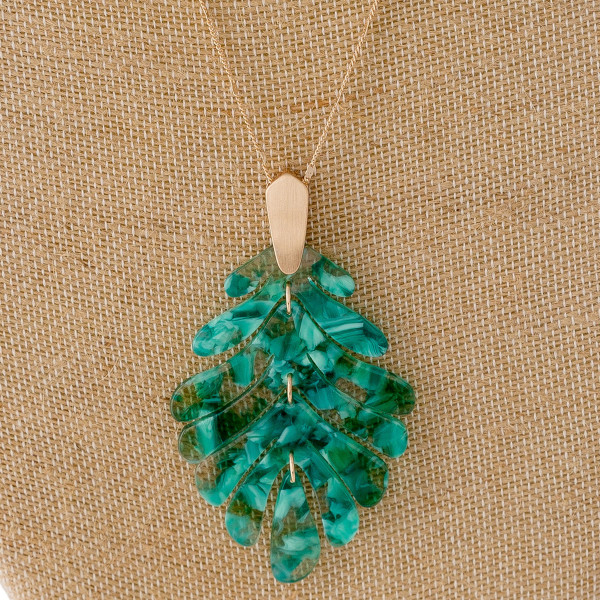 """Long dainty chain necklace featuring a flexible resin inspired leaf pendant. Pendant approximately 3.5"""". Approximately 36"""" in length overall."""
