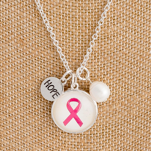 "Breast Cancer Awareness dome pendant necklace with pearl accent. Pendant approximately .75"" in diameter. Approximately 18"" in length overall."
