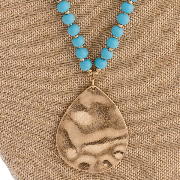"Long wood beaded necklace featuring a metal teardrop pendant. Pendant approximately 2.5"". Approximately 32"" in length overall."