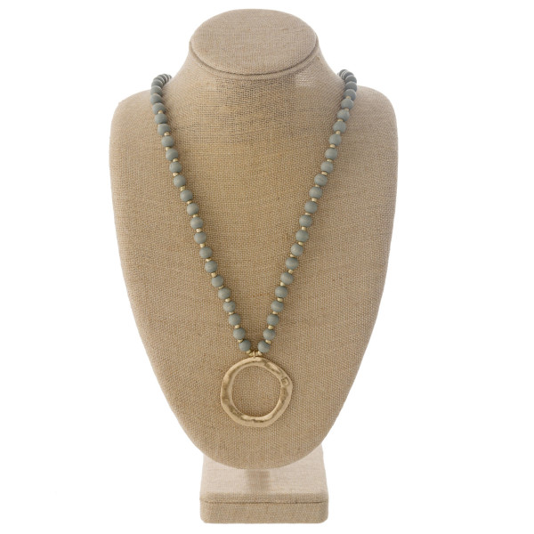 "Long wood beaded necklace featuring a metal circular pendant. Pendant approximately 2"" in diameter. Approximately 38"" in length overall."